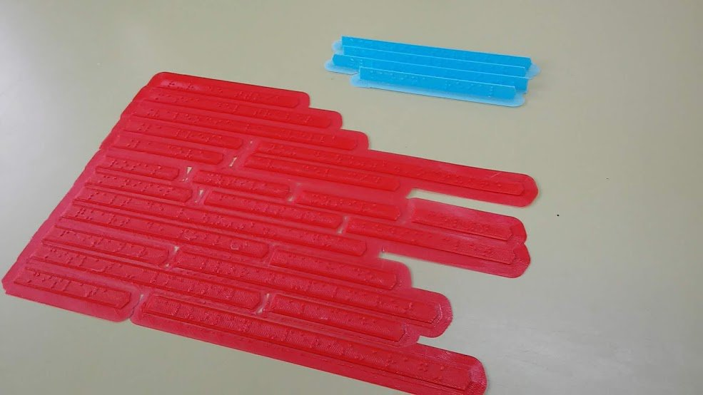 Fotografía en la que se ven etiquetas en braille impresas en horizontal y en vertical