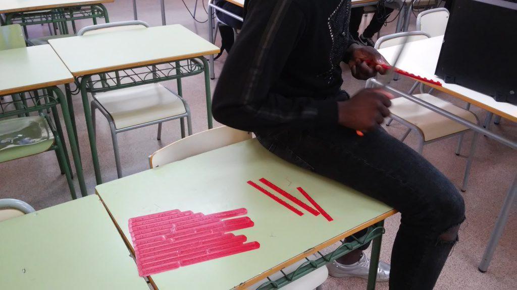 Fotografía de un alumno lijando una impresión